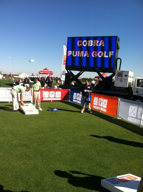 It's a party at Cobra-Puma's area. Cornhole boards, a DJ, free and free drinks.
